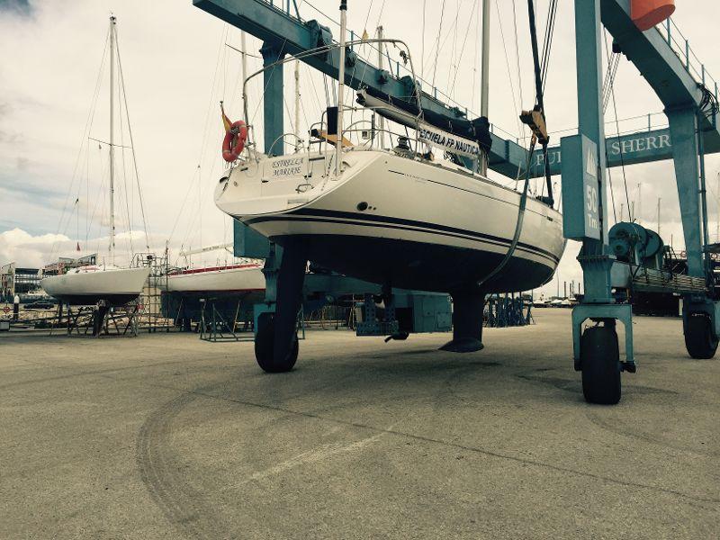 Embarcación varada, suspendida por la grúa del puerto.